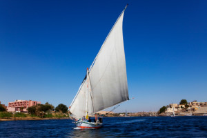 Felucca sailing the river Nile in Aswan, Nubian village on Elephantine island to the right.